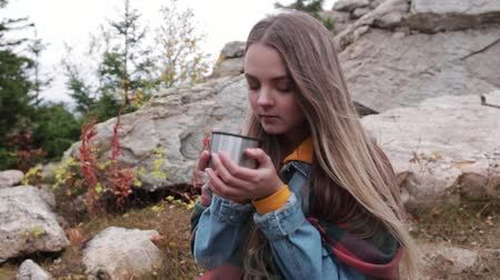 Tourist drinking tea from a mug of a bottle against the mountains Стоковые видеозаписи