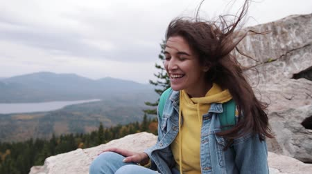 happy traveler hipster girl with windy hair and smiling standing on top of Sunny mountain. stylish women hair. atmospheric moment. travel and passion for travel.