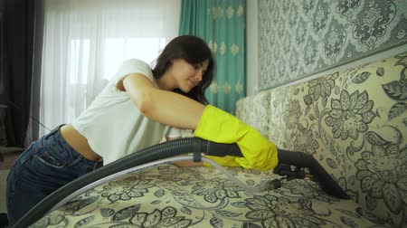 Service cleaning dirty sofa and chair with a special tool, detergent is applied. Cleaning with professional tools