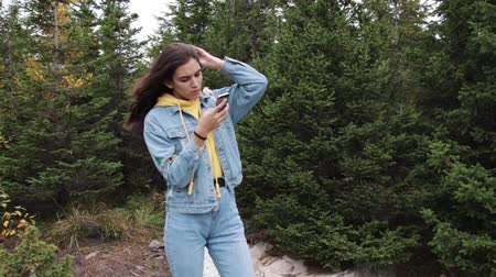 Young teen coed using touch screen smartphone while in nature. Hipster using social media and smiling while reading mobile. Beautiful woman in denim jacket in spruce forest