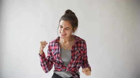 Dancing hipster girl in plaid shirt on light grey background.