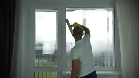 A man from a cleaning company washes Windows
