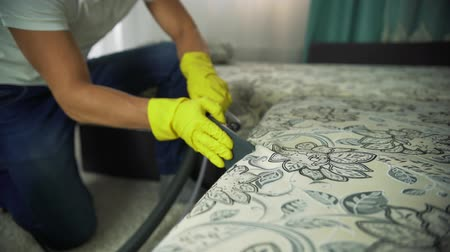 A man from a cleaning company engaged in cleaning the sofa. Man in uniform sofa cleaning cloth with dry steam cleaner. Стоковые видеозаписи