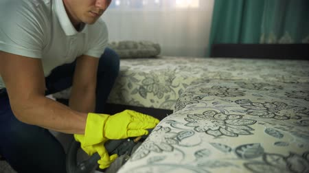 odstranění : A man from a cleaning company engaged in cleaning the sofa. Man in uniform sofa cleaning cloth with dry steam cleaner. Dostupné videozáznamy