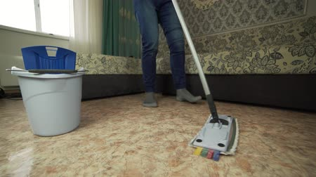 домохозяйка : Professional floor cleaning with a MOP. A man from the cleaning company washes the floor in the living room. Стоковые видеозаписи
