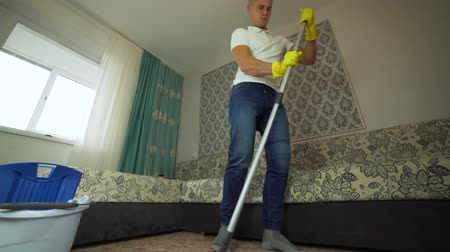 Professional floor cleaning with a MOP. A man from the cleaning company washes the floor in the living room. Стоковые видеозаписи