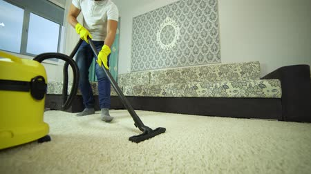 Vacuum cleaner cleans the carpet. A man from a cleaning company works, vacuuming the carpet