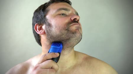 bigode : Man starting to shave beard with razor machine.