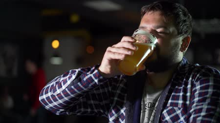 Октоберфест : Bearded man drinking beer and enjoying a drink at the pub bar. Male guest tries a glass of beer