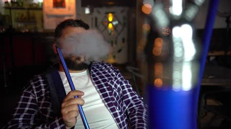 A young man smokes a hookah at the bar. Стоковые видеозаписи