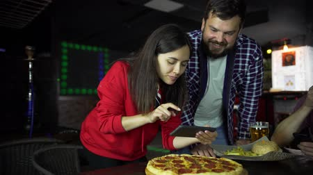 compartilhando : The girl in the pub takes pictures of pizza on your smartphone.