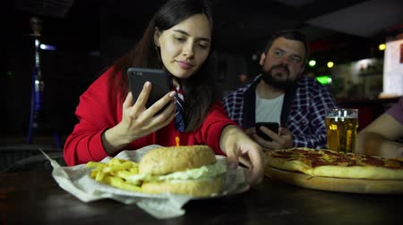 A girl in the company of a man taking pictures on your smartphone your Burger at the bar.
