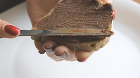 unha : Girls hands with red nails put homemade chocolate hazelnut spread on toast