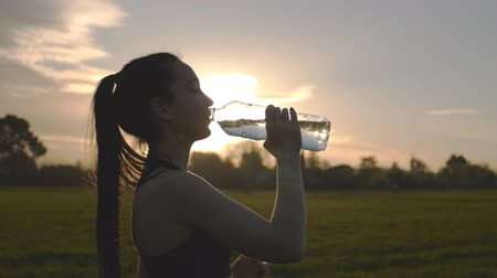 szomjúság : Girl drinks water after exercise Stock mozgókép