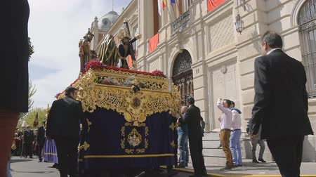 clergy : CIUDAD REAL, SPAIN - APRIL 14, 2017: Passing of sculptures of Jesus carrying cross and roman soldier with a spear during day procession of Holy Week Semana Santa .