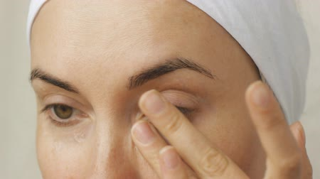 olhos castanhos : Young woman taking care of her face skin at home