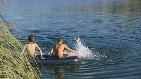 paunchy : Caucasian teen boy and girl sit on blue inflatable mattress floating on the lake dangling feet in water.