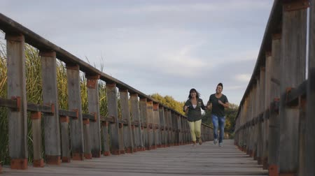 contornos : Running hispanic couple. Man and woman run hand in hand laughing on wooden bridge. Concept of love and happiness.