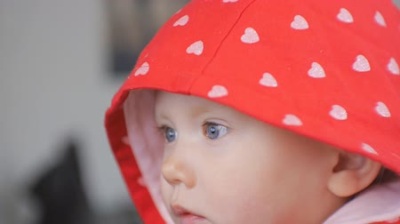 watch tv : Close-up shot of blue eyed baby face watching cartoons. The child in red hood with silver hearts pattern looking with interest what happening on the screen Stock Footage