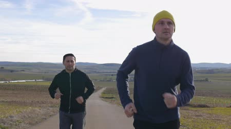 местность : Workout with personal trainer outdoors. Two men jogging in slow motion along a country road on hilly terrain background in autumn or spring