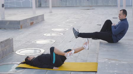 correggere : Workout with personal trainer outdoors. Woman lies on yellow mat doing air cycling. The coach demonstrating the proper technique of exercise
