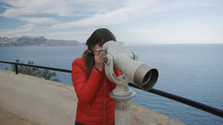 görüş uzaklığı : Young woman in red bubble jacket looking into the telescope from the observation deck on the sea background Stok Video
