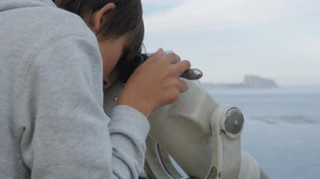 görüş uzaklığı : Close-up shot of teenager looking at the sea into the telescope from the high elevated observation deck