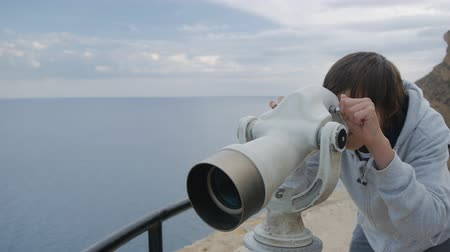 görüş uzaklığı : Fifteen-year-old boy in grey hoodie looking at the sea into the telescope from the high elevated observation deck Stok Video