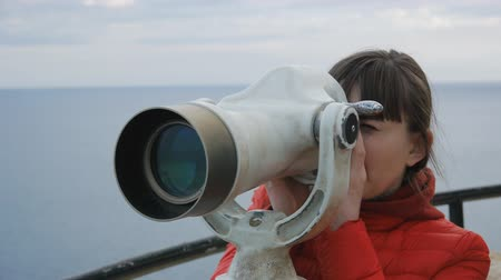 görüş uzaklığı : Close-up shot of young woman in red bubble jacket looking into the telescope from the observation deck on the sea background Stok Video