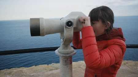 görüş uzaklığı : Young caucasian woman in red bubble jacket looking at the sea shore into the telescope from the high elevated observation deck