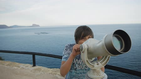 távcső : Fifteen-year-old boy looking at the sea shore into the telescope from the high elevated observation deck