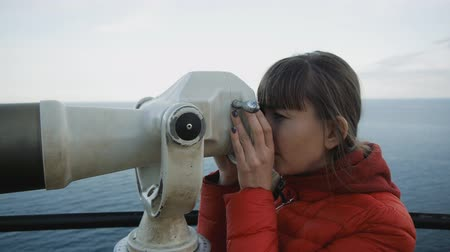 görüş uzaklığı : Young caucasian brpwn-haired woman looking at the sea coast into the telescope from the high elevated observation platform