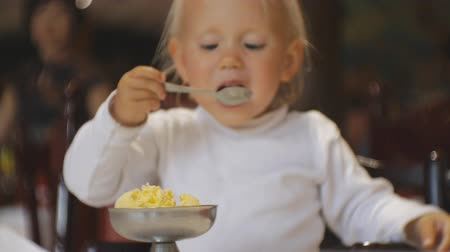 gözlü : Baby eating food in restaurant. Blonde blue-eyed child in highchair takes a teaspoon of ice cream from dish and takes it in the mouth