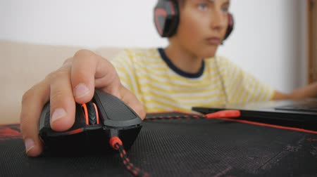 bağımlı : Teenager using laptop. Teen with headphones using wired mouse on pad. Close-up of hand clicking and scrolling computer gaming black and red mouse