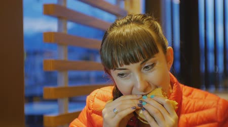 kafa yormak : Woman eating fastfood. Close-up shot of attractive female biting and chewing cheeseburger in fast food restaurant Stok Video