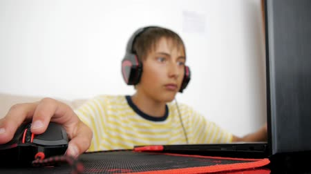 bağımlı : Teenager using laptop. Teen with headphones using wired mouse on pad. Close-up of hand moving computer gaming black and red mouse on mousepad
