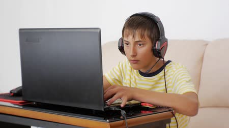 myszka komputerowa : Teenager using laptop. Video game addicted teen with headphones glued to the notebook screen pressing the keyboard