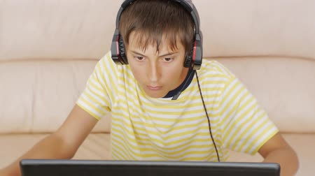зависимость : Teenager using laptop. Teen boy with headphones gravely looking to the notebook screen pressing the keyboard
