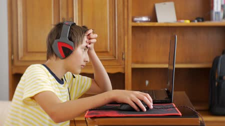 bağımlı : Teenager using laptop. Teen boy with headphones glued to the notebook screen using computer gaming mouse and scratching head
