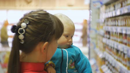 ulička : Attractive caucasian woman choosing infant food in supermarket holding her baby in arms. Close-up shot of mom and baby looking at fruit and vegetable purees on grocery store shelves