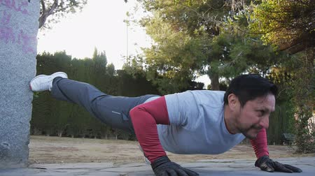 bodyweight : Workout with personal trainer outdoors. Fitness man doing raised leg push-ups in a park as part of a workout routine