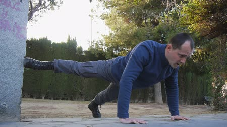 emelt : Workout with personal trainer outdoors. Male athlete in military style boots and trousers doing raised leg push-ups in a park as part of a workout routine