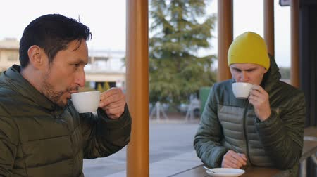 téma : Two male athletes in warm bubble jackets drink coffee after training in the outdoor area of the cafe in the evening