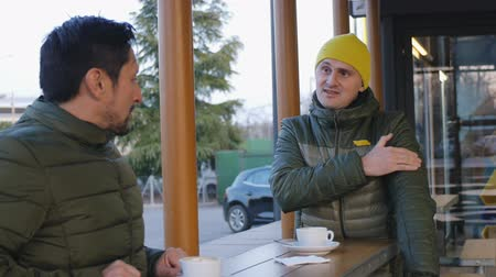 ilginç : Two male athletes in warm bubble jackets talk after training in the outdoor area of the cafe in the evening. The guy with yellow knit cap tells something about the workout Stok Video