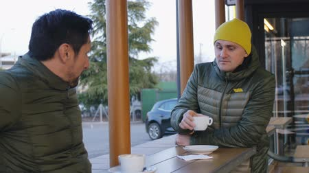 téma : Two male athletes in warm bubble jackets talk after training in the outdoor area of the cafe in the evening. The guy with the beard tells something about the workout