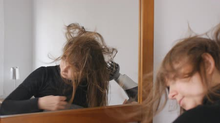 penteado : Young attractive brown-haired woman turns her head drying hair with a hair dryer in front of the mirror