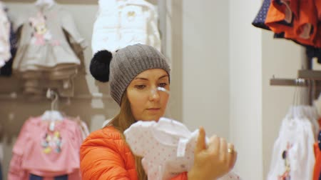 gruccia abiti : Attractive woman in baby clothes store. Caucasian female in gray knit hat and red jacket holds baby dress in hands examining it Filmati Stock