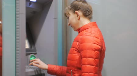 bankomat : Woman using cash machine. Attractive young female in red bubble jacket inserting credit card into ATM. Woman smiling entering pin code