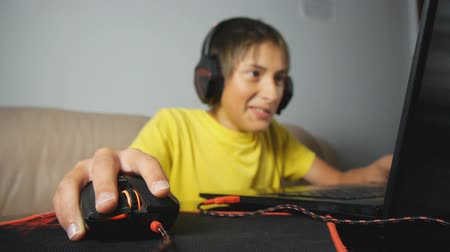 bağımlı : Teenager using laptop at night. Teen with headphones using wired mouse on pad. Close-up of hand clicking and scrolling computer gaming black and red mouse Stok Video