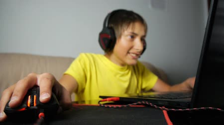 bağımlı : Teenager using laptop at night. Teen with headphones emotionally reacting moving wired mouse on pad. Close-up of hand and computer gaming black and red mouse